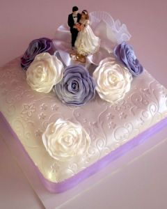 Svatební dort hranatý jednopatrový s lila stuhou a bílými a fialovými růžemi z marcipánu