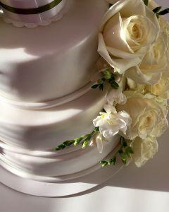 svatební dort s figurkami a živými růžemi a fréziemi