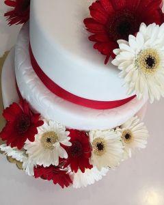 svatební dort - červené stuhy a gerbery