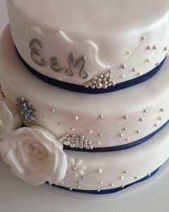 svatební dort - modrá stuha, perličky a dvě bílé růže